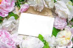 Blank greeting card and envelope in frame of pink and white pe. Onies and roses over rustic wooden background. flat lay. top view with copy space. wedding Stock Photos