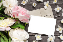 Blank greeting card and envelope in frame of pink and white peonies and jasmine flowers. Over rustic wooden background. flat lay. top view with copy space Royalty Free Stock Photo