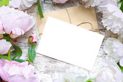 Blank greeting card and envelope in frame of pink and white peonies and roses. Over white wooden background. flat lay. top view with copy space. wedding Royalty Free Stock Photography