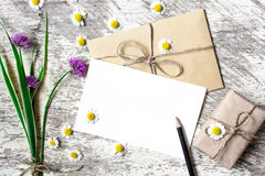 Blank greeting card and envelope with white chamomile flowers and purple wildflowers Stock Image