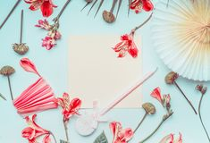 Blank greeting card mock up with paper party fan, tropical leaves and coral color flowers , top view. Flat lay. Frame. Copy space. For your text or design royalty free stock photography