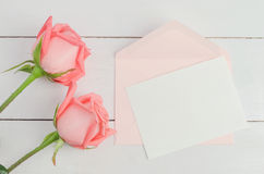 Blank greeting card with pink envelope and pink rose flowers. On white wooden background with soft vintage tone, Valentine rose and card stock images