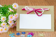 Blank greeting card. With pink ribbon and flower on wooden background Stock Image