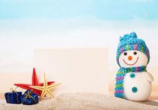 Blank greeting card, starfish, snowman, gifts in  sand of  sea. Royalty Free Stock Images