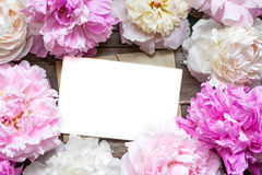 Blank greeting card or wedding invitation and envelope in frame of tender peonies flowers. Over rustic wooden background. mock up. flat lay. top view with copy Stock Photos