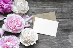 Blank greeting card or wedding invitation and envelope with tender peonies flowers. Over rustic wooden background. mock up. flat lay. top view with copy space Stock Photos