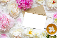 Blank greeting card or wedding invitation with tender peonies and roses flowers with cup of green jasmine tea. Mock up. flat lay. top view Stock Photos