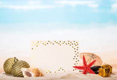 Blank greeting,  star, Christmas toys, gifts in sand against  sea. Royalty Free Stock Photos