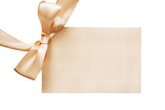 Blank greetings card. Blank beige greetings card with silk bow on white background Royalty Free Stock Photo