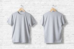 Blank grey T-Shirts Mock-up hanging on white wall, rear and front side view. Ready to replace your design royalty free stock images
