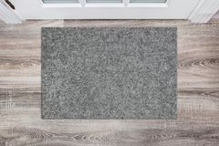 Blank grey woolen doormat before the white door in the hall. Mat on wooden floor, product Mockup.  royalty free stock photos