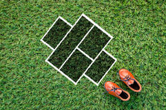 Blank grid and leather shoe on grass field Stock Image