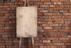 Blank grunge easel on a brick wall Royalty Free Stock Image