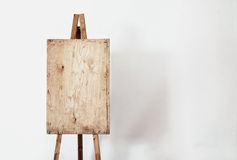 Blank grunge easel in a light room Stock Images
