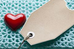 Blank paper label and red heart on blue background stock photos