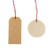 Blank hanging gift tags. Made from brown eco-friendly kraft paper in different shapes with red twine - isolated on white background Royalty Free Stock Photography