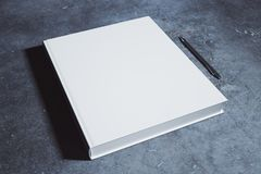 Blank hardcover diary. Blank white hardcover diary and pen placed on concrete desk. Supplies, stationery items, paperwork concept. Mock up, 3D Rendering Royalty Free Stock Photo