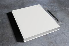 Blank hardcover notepad. Blank white hardcover notepad and pen placed on concrete desk. Supplies, stationery items, paperwork concept. Mock up, 3D Rendering Stock Photo