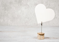 Blank heart shaped frame on wooden table against vintage wall royalty free stock photo