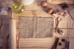 Blank hemp sackcloth and bakery ingredients on wooden table back Royalty Free Stock Images
