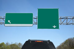 Blank Highway Exit Signs. Blank green highway sign against blue sky with rear view of car. Cope space. Horizontal Stock Photos