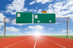 Blank highway and road sign with Running track  green grass and Stock Photos