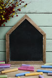 Blank house-shaped chalkboard and chalk Stock Photo