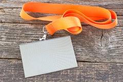 Blank  ID card tag with ribbon. On wooden background Stock Photography