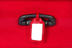 Blank identification tag over red suitcase Royalty Free Stock Photo
