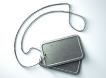 Blank Identity Dog Tags Isolated. A regular set of blank military dog tag identity tags attached to a chain draped on an isolated background Stock Image