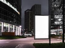 Blank illuminated banner at night time near to skyscrapers. 3d rendering stock image