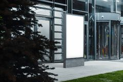 Blank illuminated banner stand next to modern building at night, 3d rendering. stock image