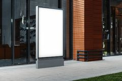 Blank illuminated banner stand next to modern building at night, 3d rendering. stock photos