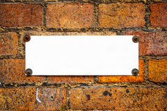 Blank information board on brick wall Royalty Free Stock Photo