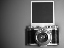 Blank instant photo frame on gray background highlighted with old retro vintage camera and copy space. In black and white Royalty Free Stock Images