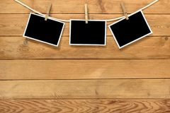 Blank instant photo frames. Blank instant photo frames on brown wooden background royalty free stock image