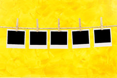 Polaroid frame photo prints rope string washing line. Several blank polaroid instant camera photo prints hanging on a rope or washing line  against a painted Royalty Free Stock Photo