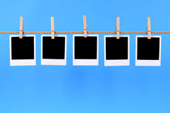 Polaroid frame photo prints rope string washing line. Several blank polaroid instant camera photo prints hanging on a rope or string isolated against a blue Royalty Free Stock Photography
