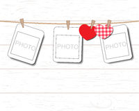 Blank instant photo and small red paper heart hanging on the clothesline Stock Photos