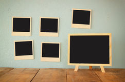 Blank instant photos hang over wooden textured background next to blank blackboard Stock Photos