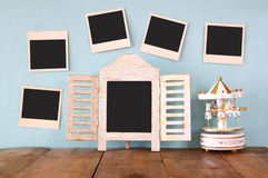 Blank instant photos hang over wooden textured background next to blank blackboard and vintage white carousel horses Stock Photos