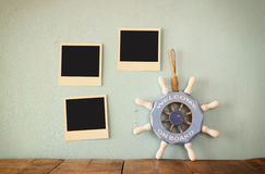 Blank instant photos hang over wooden textured background next to vintage steering wheel with the phrase welcome aboard written on Stock Images