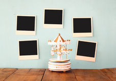 Blank instant photos hang over wooden textured background next to vintage white carousel horses Stock Photos