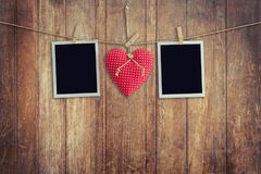 Blank instant photos and red heart hanging on wooden background. Royalty Free Stock Photo
