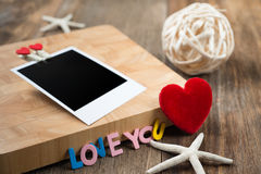 Blank instant photos with red hearts.On wooden background Royalty Free Stock Images