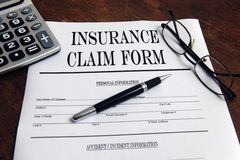 Blank insurance claim form and pen. On desktop with calculator