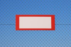 Blank interdiction sign. On a fence with clear blue sky as background Stock Photography