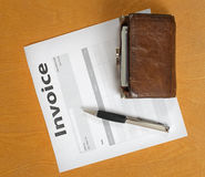 Blank invoices and old purse lying on a wooden surface