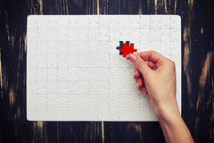 Blank jigsaw puzzle with white pieces, but with one red piece Royalty Free Stock Images