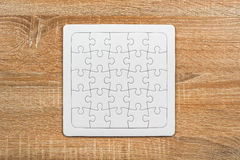 Blank jigsaw puzzle on wooden table Royalty Free Stock Photography